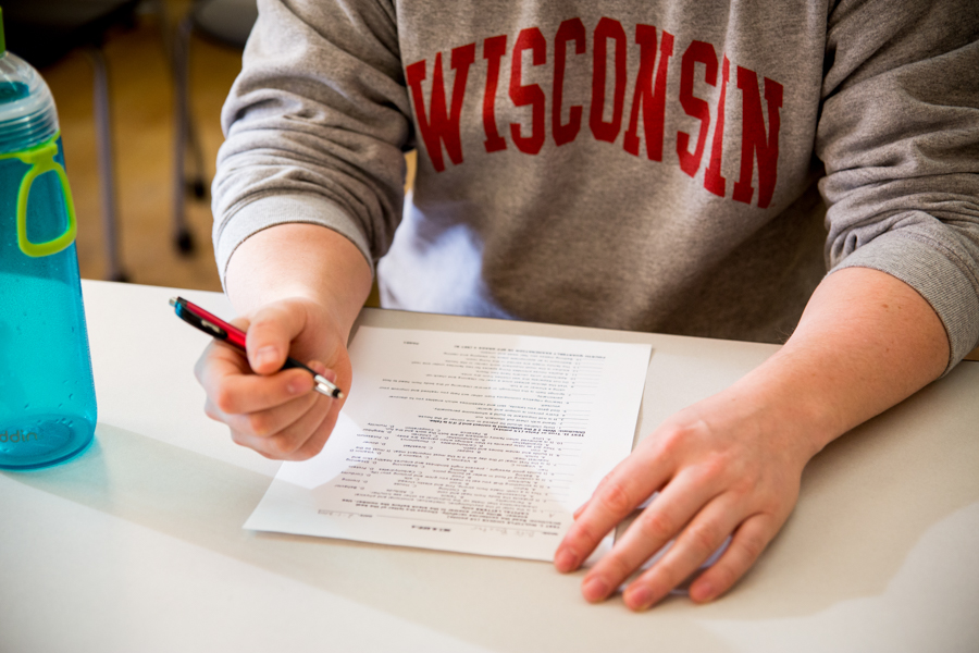 Person in a Wisconsin sweatshirt filling out a form