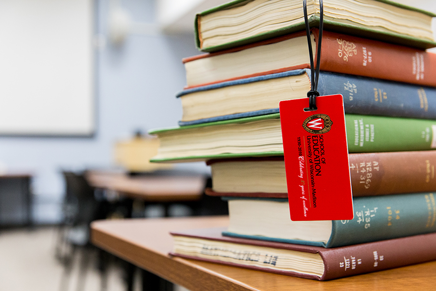 Books stacked with a School of Education luggage tag