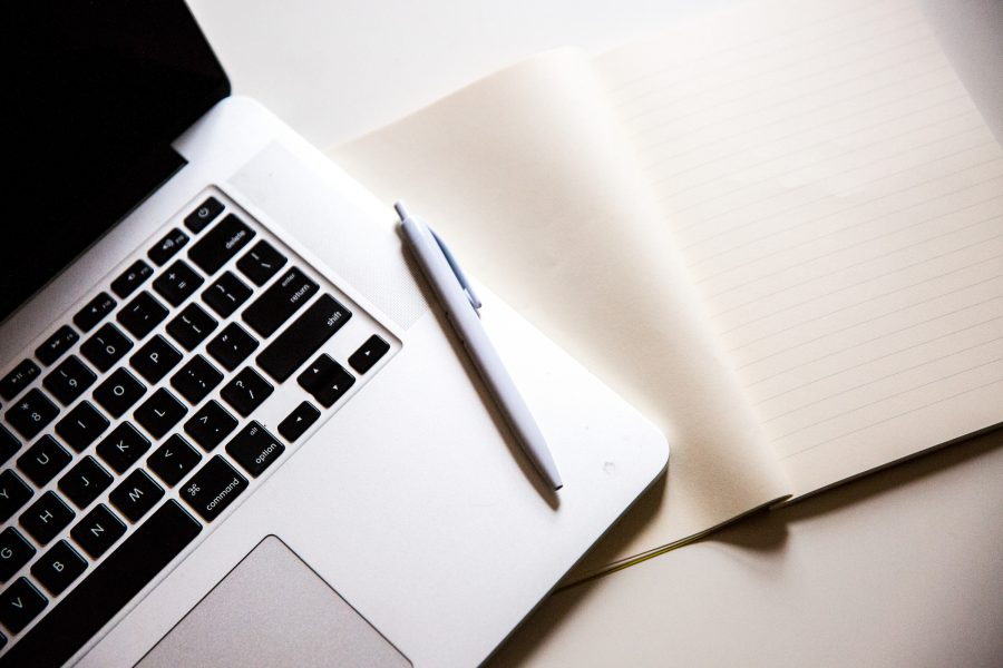 Photograph of a laptop, pen, and notebook.